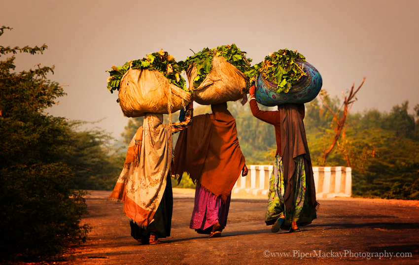 Women carring produce walking alon the highway